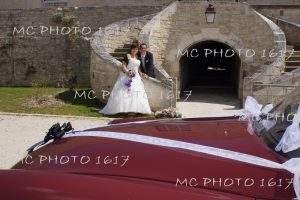 couple mariés en fond escalier en pierre avec devant voiture rouge