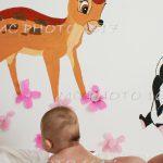 nourisson sur table à langer sans couche avec un mur peint avec bambi charente