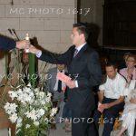 parrain-donnant-la-bougie-au-cure-bapteme-ceremonie-eglise