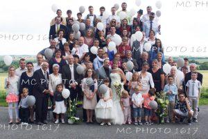 photo-groupe-mariage-avec-remorque-gradins-invites-tiennent-ballons-gris-et-blanc