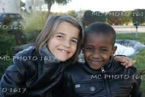 portrait-deux-enfants-en-exterieur-unepetite-fille-blanche-et-un-garcon-noir-qui-se-tiennent-par-les-apaules
