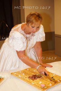 femme-habillee-en-robe-de-mariee-qui-coupe-un-gateau-anniversaire-de-mariage-cherente-maritime