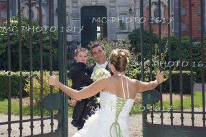 marie-qui-tient-un-enfan-dans-ses-bras-mariee-de-dos-on-voit-lacets-verts-qui-ouvre-une-grille-cognac-charente