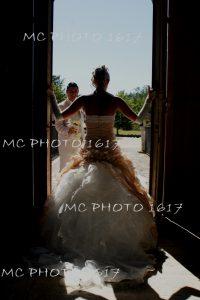 mariee-de-dos-en-contre-jour-dans-encadrement-porte-marie-devant-avec-bouquet-de-fleurs-charente-cognac