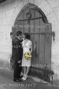 photo-noir-et-blanc-couple-maries-devant-une-porte-en-bois-cognac-charente